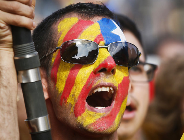 "A man with his face painted in the colours of the ""Estelada"", or Catalan separatist flag, takes part in a Catalan pro-independence demonstration in Barcelona October 19, 2014. (Photo by Albert Gea/Reuters)"
