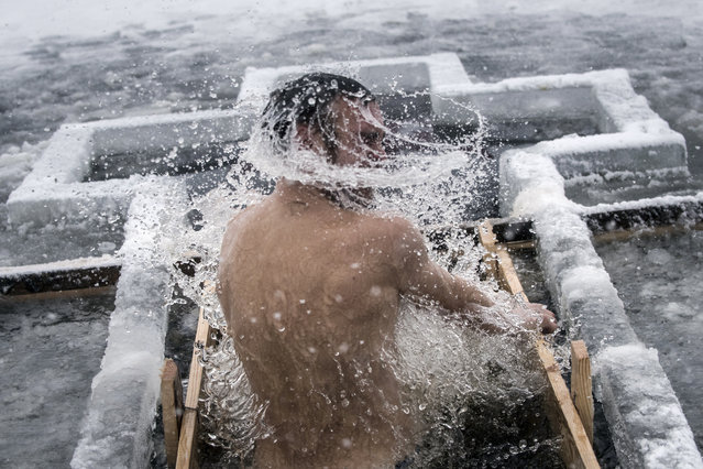 An Orthodox believer bathes in the icy water on Epiphany at a hole in Dnipro river in Kiev, Ukraine, Friday, January 19, 2018. Thousands of Ukrainian Orthodox Church followers plunged into icy rivers and ponds across the country to mark Epiphany, cleansing themselves with water deemed holy for the day. (Photo by Evgeniy Maloletka/AP Photo)