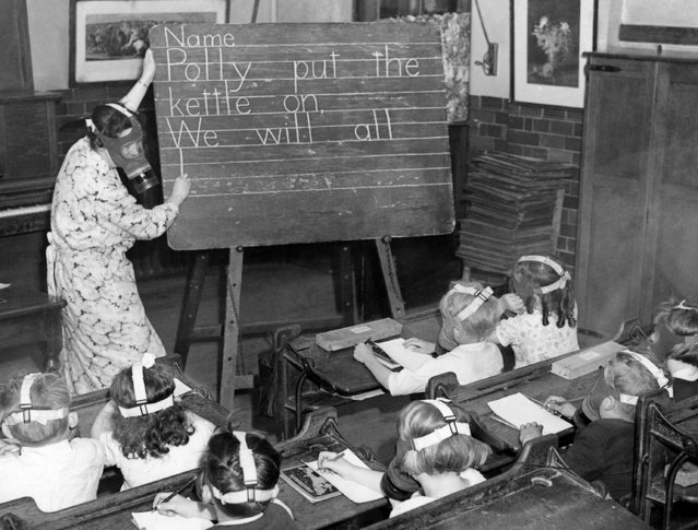 The children proceed with their lesson in writing,  all are wearing their gas masks which does not seem to embarrass them in the least in England on July 1, 1941. The main object is to keep their  minds constantly occupied, so they forget all about the masks. (Photo by Laurence Harris/AP Photo)