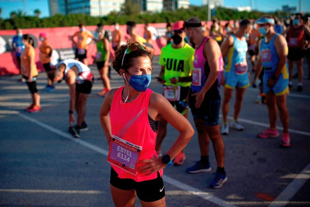 "Athletes wearing face masks to prevent the spread of coronavirus keep their positions before taking part in the Merce run in Barcelona on September 20, 2020. The race ""La Cursa de la Merce"" runs across 10km in Barcelona city and this year is dedicated to the fight against COVID-19. (Photo by Josep Lago/AFP Photo)"