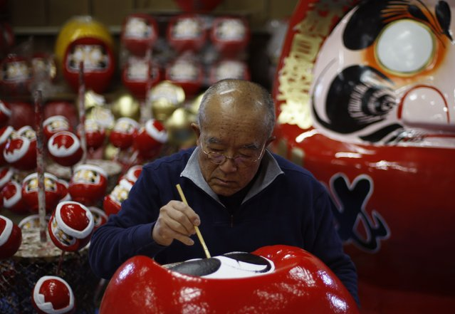 """Japanese craftsman Sumikazu Nakata adds the final touches on a Daruma doll, which is believed to bring good luck, at his studio  """"Daimonya"""" in Takasaki, northwest of Tokyo November 23, 2014. (Photo by Yuya Shino/Reuters)"""