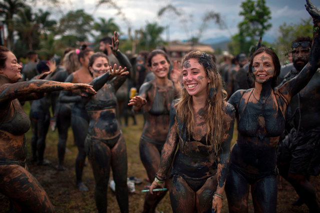 """Revellers celebrate during the """"Bloco da Lama"""", a mud carnival, in Paraty, Brazil, on February 10, 2018. (Photo by Mauro Pimentel/AFP Photo)"""