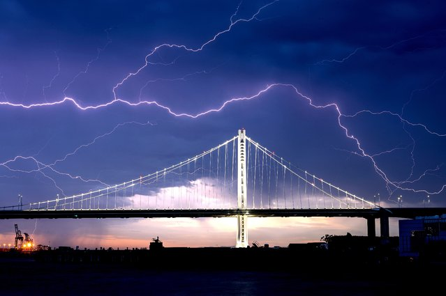 Lightning forks over the San Francisco-Oakland Bay Bridge as a storm passes over Oakland, Calif., Sunday, August 16, 2020. Numerous lightning strikes early Sunday sparked brush fires throughout the region. (Photo by Noah Berger/AP Photo)