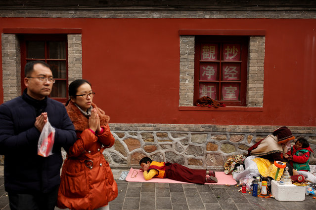 Chinese people make a gesture of prayer as they walk past a Tibetan family at a Buddhist temple in Badachu park during Spring Festival celebrations marking Chinese New Year in Beijing, China, February 17, 2018. (Photo by Thomas Peter/Reuters)