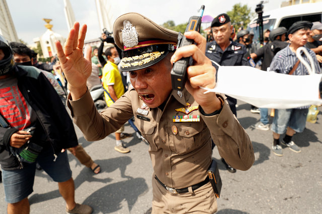 A police officer reacts during clashes between pro-democracy demonstrators and royalists during a Thai anti-government mass protest, on the 47th anniversary of the 1973 student uprising, in Bangkok, Thailand on October 14, 2020. (Photo by Jorge Silva/Reuters)