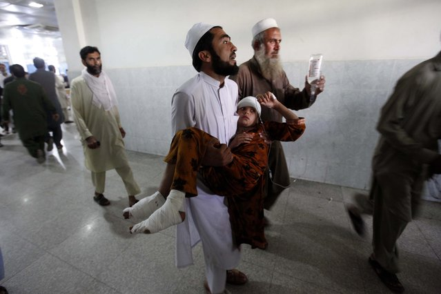 People carry a girl who was injured in a 7.7 magnitude earthquake,  to a hospital in Peshawar, Pakistan, 26 October 2015. (Photo by Arshad Arbab/EPA)