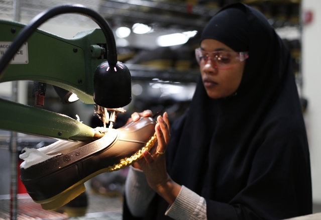 In this Tuesday, December 2, 2014 photo, Muslima Hassan trims the rubber bottom of an L.L. Bean boot at a facility in Lewiston, Maine. The Maine-based retailer can't make enough of its iconic boots to keep up with demand this holiday season. Some styles are on back order until February, and the company is answering by hiring more than 100 workers and purchasing a new machine that makes the rubber soles. (Photo by Robert F. Bukaty/AP Photo)