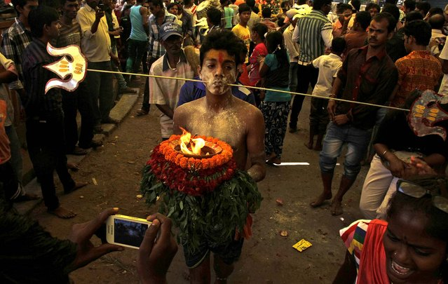 A Hindu devotee, cheeks pierced with a metal rod, participates in a religious procession dedicated to Goddess Mutthumariamman in Bandel, India, on April 5, 2013. The ritualistic acts of inflicting pain on oneself are performed as an act of penance with the belief that it will prevent diseases and for the well-being of the families of devotees. (Photo by Bikas Das/Associated Press)
