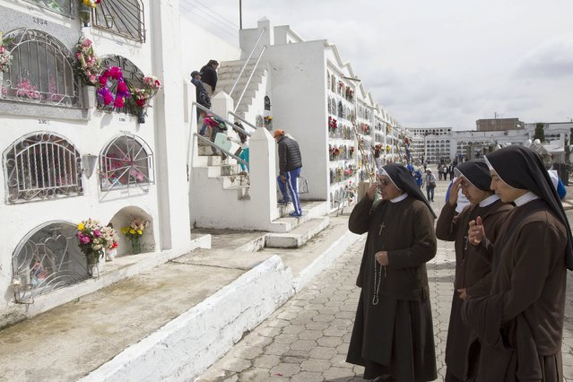 Nuns pray in front of graves at a cemetery known for its topiary art, during the observance of the Day of the Dead, in Tulcan, Ecuador November 2, 2015. (Photo by Guillermo Granja/Reuters)