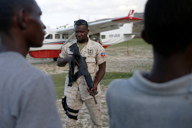 A police officer stands guard in front of a plane loaded with food at the airport after Hurricane Matthew passes Jeremie, Haiti, October 7, 2016. (Photo by Carlos Garcia Rawlins/Reuters)
