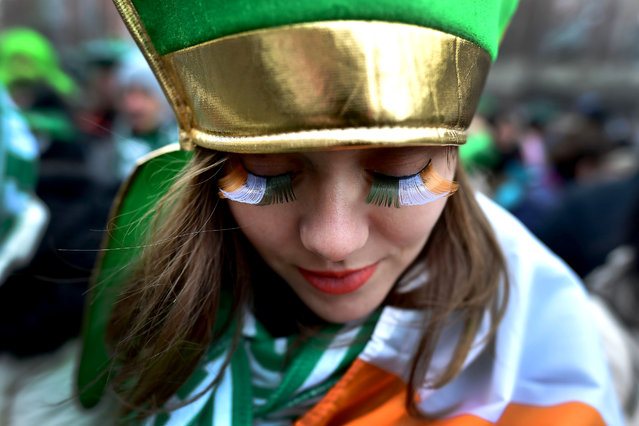 A spectator shows off her green, white and gold eyelashes as the annual Saint Patrick's day parade takes place on March 17, 2018 in Dublin, Ireland. Dublin hosts the largest Saint Patrick's day parade in the world with a route spanning 2.5 km. The Irish annals for the fifth century date Patrick's arrival in Ireland in the year 432 with the patron saint of Ireland's remains believed to be buried at Down Cathedral in County Down. (Photo by Charles McQuillan/Getty Images)