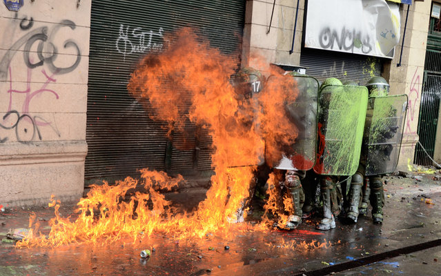 Students clash with riot police during a protest to demand Chilean President Sebastian Pinera's government to improve the public education quality, in Santiago, on April 11,2013. (Photo by Pablo Tapia/AFP Photo)