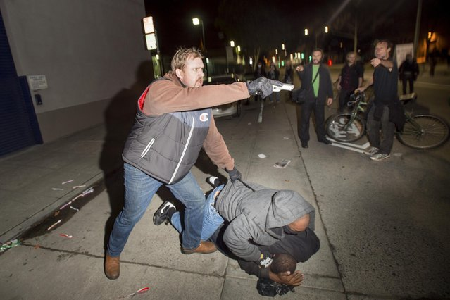 An undercover police officer, who had been marching with anti-police demonstrators, aims his gun at protesters after some in the crowd attacked him and his partner in Oakland, California December 10, 2014. Police said more than 100 demonstrators marched in Berkeley, California, which has a history of social activism. (Photo by Noah Berger/Reuters)