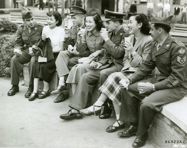 "Airmen and their Japanese  dates ""do"" the town together, visiting the local points of interest. Almost every community in Japan has it's famous shrines and parks.  Tachikawa boasts beautiful environment. Girls are wearing western dress, May 1952. (Photo by National Archives and Records Administration)"