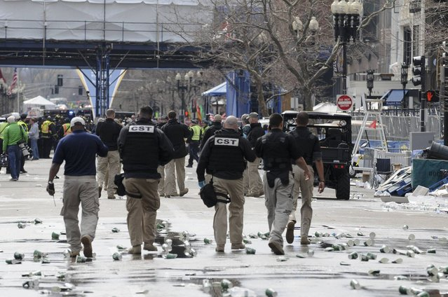 Public safety officials evacuate the scene after several explosions near the finish line of the 117th Boston Marathon in Boston, Massachusetts April 15, 2013. (Photo by Neal Hamberg/Reuters)