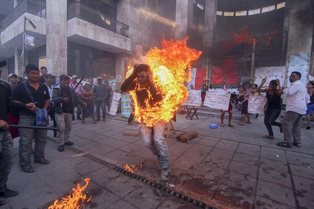 In this December 5, 2014 file photo, farmer Agustin Gomez Perez runs engulfed in flames after he was lit on fire as a form of protest outside the Chiapas state legislature in Tuxtla Gutierrez, Mexico. Perez, 21, was demanding the release of his father, indigenous leader Florentino Gomez Giron, who was arrested last year on charges stemming from a series of demonstrations in 2011 that turned violent. (Photo by Jacob Garcia/AP Photo/Cuartoscuro)