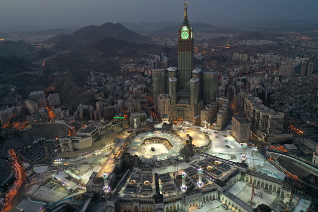 This picture taken on May 24, 2020 during the early hours of Eid al-Fitr, the Muslim holiday which starts at the conclusion of the holy fasting month of Ramadan, shows an aerial view of Saudi Arabia's holy city of Mecca, with the Abraj al-Bait Mecca Royal Clock Tower overlooking the Grand Mosque and Kaaba in the centre. Saudi Arabia began a five-day, round-the-clock curfew from May 23 after COVID-19 coronavirus infections more than quadrupled since the start of Ramadan to around 68,000 – the highest in the Gulf. (Photo by AFP Photo/Stringer)