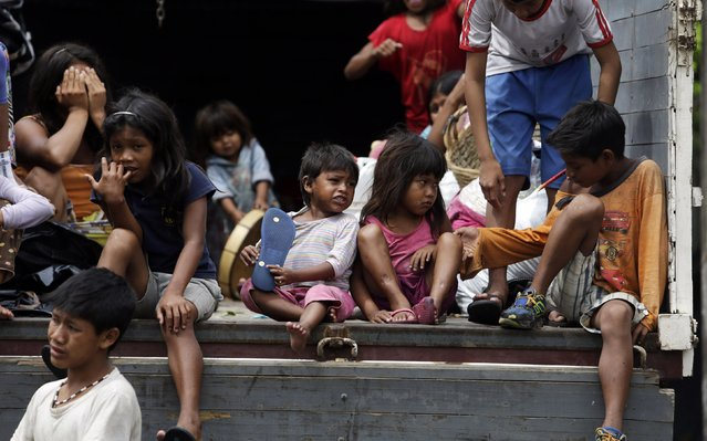 Members of the indigenous community Guarani sit in a military truck as they are sent back to Caaguazu, in Asuncion December 18, 2014. (Photo by Jorge Adorno/Reuters)