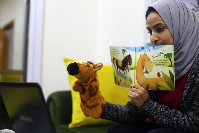 A Palestinian Teacher, Beniyas Abu Harb, 27, teaches an online class from his home, a preventive measure amid fears of the spread of the novel coronavirus, in Gaza city, on November 26, 2020. (Photo by APAImages/Rex Features/Shutterstock)