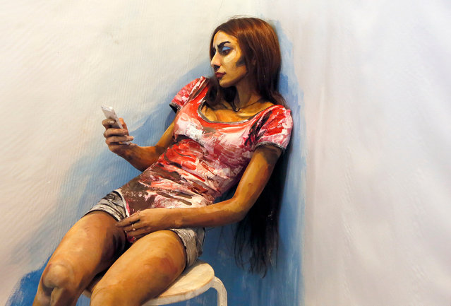 "Model Inna Magomedova uses her mobile phone while she presents ""The Alive Painting"" body art work by Russian artist Maria Gasanova during the Art Krasnoyarsk annual festival in Siberian city of Krasnoyarsk, Russia, October 26, 2016. (Photo by Ilya Naymushin/Reuters)"