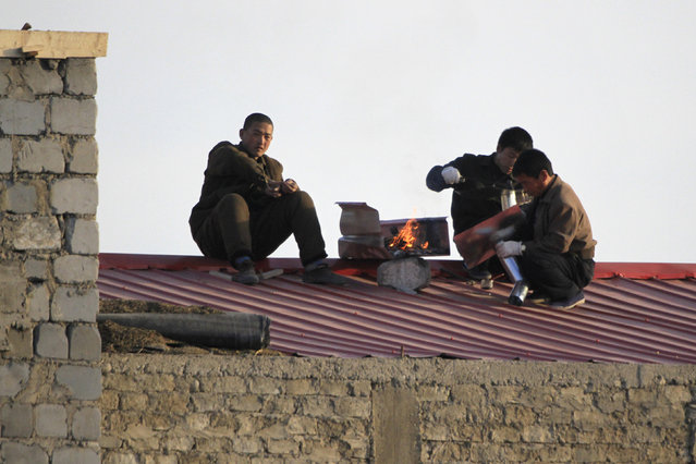 North Koreans work on the roof of a house along the banks of the Yalu River, near the North Korean town of Sinuiju, opposite the Chinese border city of Dandong, November 23, 2010. (Photo by Reuters/Stringer)