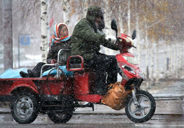 A couple ride a motorcycle along a street during snow in Altay, Xinjiang Uighur Autonomous Region, China, November 8, 2015. Picture taken November 8, 2015. (Photo by Reuters/Stringer)