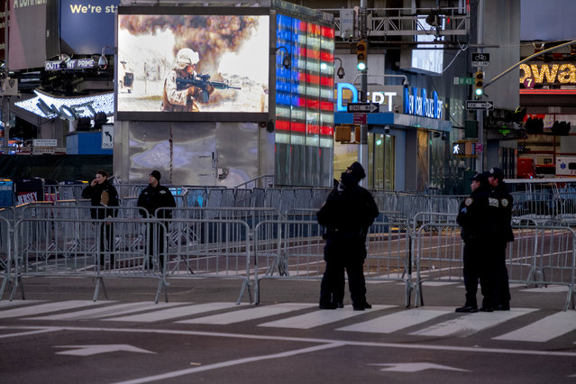 Police officers stand along a mostly empty Seventh Avenue during what would normally be a Times Square packed with people in New York, late Thursday, December 31, 2020, as celebrations have been truncated this New Year's Eve due to the ongoing pandemic. (Photo by Craig Ruttle/AP Photo)