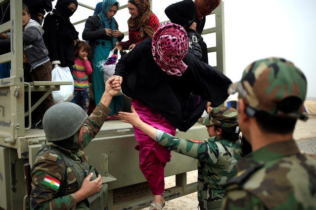 Kurdish Peshmerga soldiers help a newly internally displaced woman to jump from the truck upon ther arrival at Al Khazar camp near Hassan Sham, east of Mosul, east of Mosul, Iraq October 28, 2016. (Photo by Zohra Bensemra/Reuters)