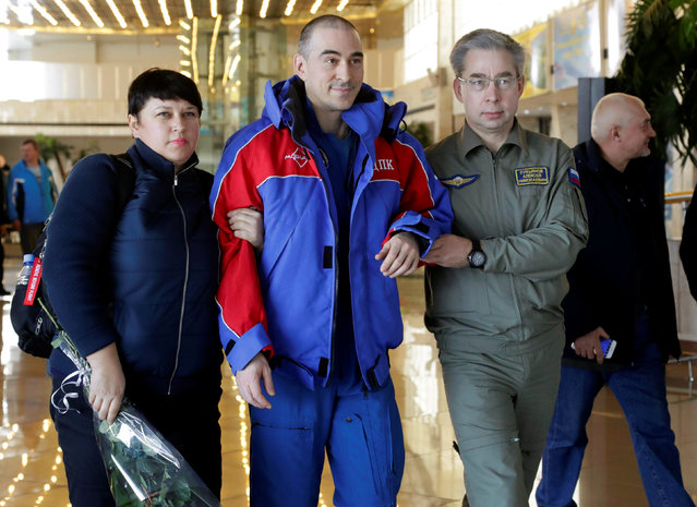 International Space Station (ISS) crew member Anatoly Ivanishin of Russia is assisted by Russian specialists upon his arrival at the airport in Karaganda, Kazakhstan, October 30, 2016. (Photo by Dmitri Lovetsky/Reuters)
