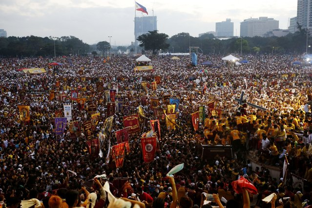 Devotees carry the Black Nazarene (R) to be placed on a carriage before an annual procession in Manila, January 9, 2015. (Photo by Erik De Castro/Reuters)