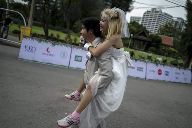"A man carries his fiancee as they participate in the ""Running of the Brides"" race in a park in Bangkok, Thailand, November 28, 2015. (Photo by Athit Perawongmetha/Reuters)"