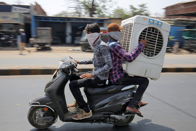 Men transport an air cooler on a two wheeler during a hot summer day in Ahmedabad, India May 24, 2018. (Photo by Amit Dave/Reuters)