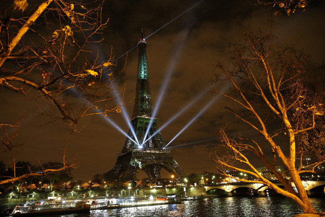 The Eiffel Tower lights up with colors and messages of hope on the eve of the COP21 climate conference in Paris, France, 29 November 2015. The 21st Conference of the Parties (COP21) due to be held in Paris from 30 November to 11 December will proceed as planned, despite the terrorist attacks of 13 November. (Photo by Yoan Valat/EPA)