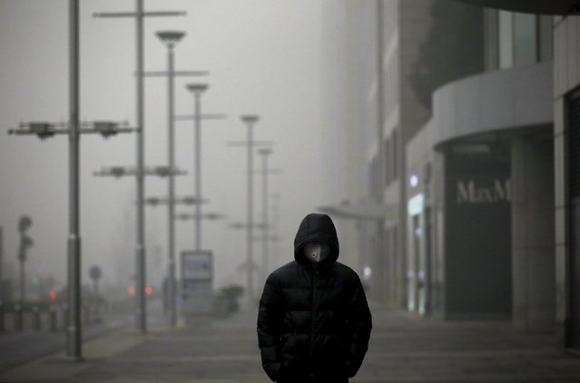 A man wearing a protective mask walks as smog covers China's capital Beijing on an extremely polluted day, December 1, 2015. (Photo by Jason Lee/Reuters)
