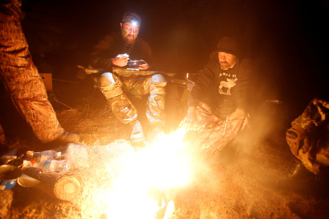 Members of the Oath Keepers and general public rest and warm up by the fire during a tactical training session in northern Idaho, U.S. October 1, 2016. (Photo by Jim Urquhart/Reuters)