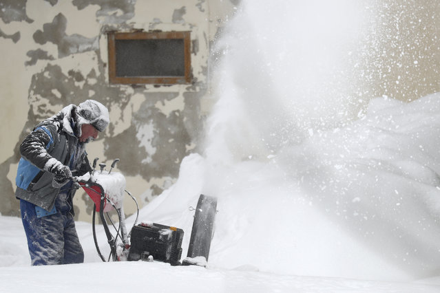 A man blows snow from his driveway at his house near Altenberg, Germany, Monday, February 8, 2021. (Photo by Matthias Schrader/AP Photo)