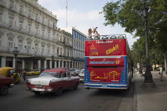 Tourists take pictures atop a double decker sightseeing bus in Havana January 15, 2015. The United States announced sweeping new rules on Thursday that will significantly ease sanctions on Cuba, opening up the communist-ruled island to expanded U.S. travel, trade and financial activities. (Photo by Alexandre Meneghini/Reuters)