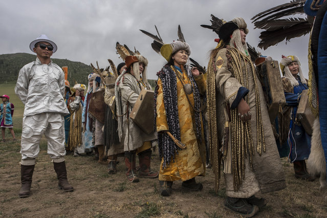 Mongolian Shamans or Buu, gather before a fire ritual meant to summon spirits to mark the period of the Summer Solstice on June 23, 2018 outside Ulaanbaatar, Mongolia. (Photo by Kevin Frayer/Getty Images)