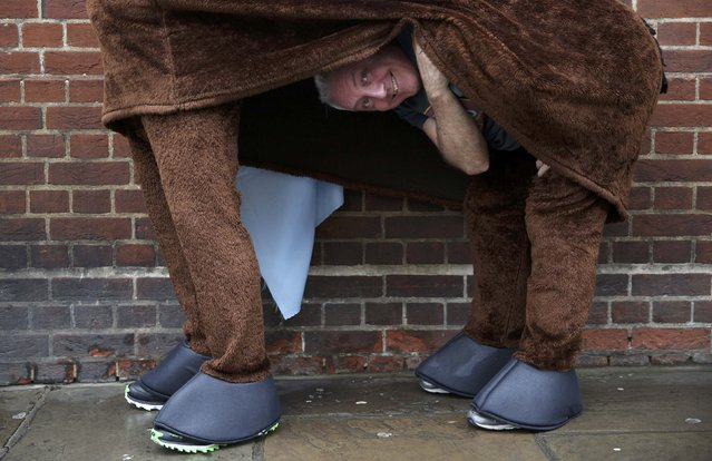 A participant peeks from his costume before the start of the the annual London Pantomime Horse Race in Greenwich, Britain December 13, 2015. (Photo by Neil Hall/Reuters)