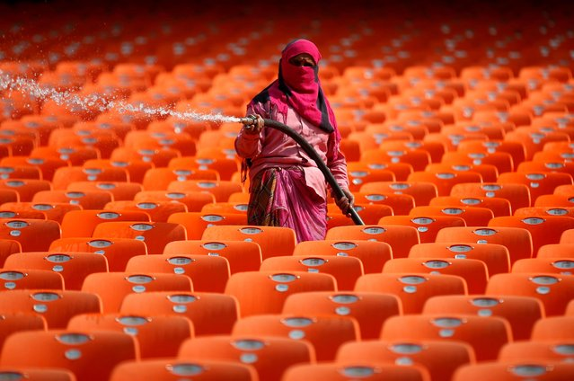 A worker cleans the seats in the stands at Sardar Patel Gujarat Stadium, where India and England are scheduled to play their third test match, in Ahmedabad India, February 17, 2021. (Photo by Amit Dave/Reuters)