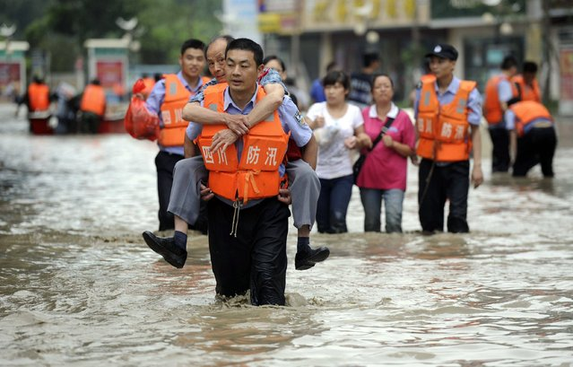 A policeman carries a man on his back as he walks on a flooded street after heavy rainfalls hit Chengdu, Sichuan province, July 9, 2013. (Photo by Reuters/China Daily)