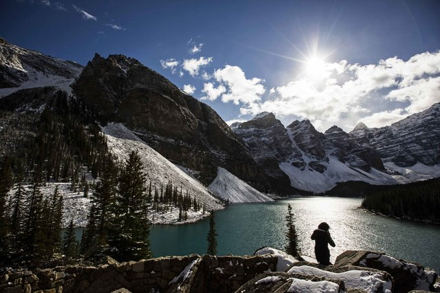 A woman looks over Moraine Lake in Banff National Park, in the Canadian Rocky Mountains outside the village of Lake Louise, Alberta, October 2, 2014. (Photo by Mark Blinch/Reuters)