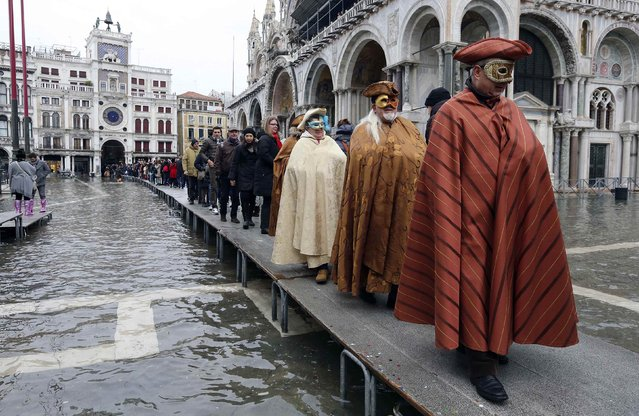 Masked revellers walk on raised platforms above flood waters during a period of seasonal high water and on the first day of carnival, in Venice February 1, 2015. (Photo by Stefano Rellandini/Reuters)