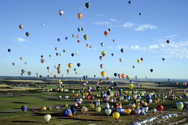 "Over four hundred  hot-air balloons prepare to take off in Chambley-Bussieres, eastern France, on Wednesday, July 31, 2013 in an attempt to set a world record for collective taking-off during the event ""Lorraine Mondial air ballons"", an international hot-air balloon meeting. (Photo by Alexandre Marchi/AP Photo/L'est Republicain)"