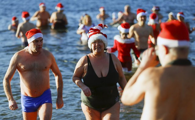 "Members of the ice swimming club ""Berliner Seehunde"" (Berlin Seals) take a dip in the Orankesee lake as part of their traditional Christmas swimming session in Berlin, Germany, December 25, 2015. (Photo by Hannibal Hanschke/Reuters)"