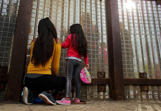 Families separated by the two countries chat along the U.S.-Mexico border fence at Border Field State Park, California, U.S., November 19, 2016. (Photo by Mike Blake/Reuters)