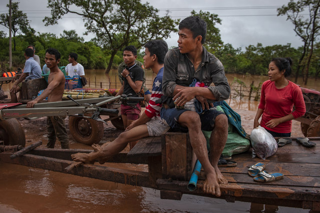Villagers evacuate to safer grounds after flash floods engulfed their villages the other night, on July 26, 2018 in Attepeu, southeastern Laos. (Photo by Jes Aznar/Getty Images)