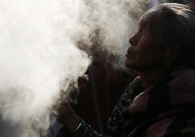 Smoke rises from burning incense as a woman offers prayer during the opening of Boudhanath stupa, which underwent renovation after suffering damage during the 2015 earthquake, in Kathmandu, Nepal November 22, 2016. (Photo by Navesh Chitrakar/Reuters)