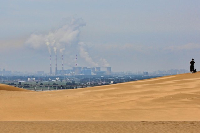 A toursit walks on the dunes near a power plant in Xiangshawan Desert, also called Sounding Sand Desert on July 17, 2013 in Ordos of Inner Mongolia Autonomous Region, China. Xiangshawan is China's famous tourist resort in the desert. It is located along the middle section of Kubuqi Desert on the south tip of Dalate League under Ordos City. Sliding down from the 110-metre-high, 45-degree sand hill, running a course of 200 metres, the sands produce the sound of automobile engines, a natural phenomenon that nobody can explain. (Photo by Feng Li/Getty Images)