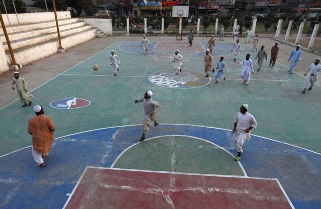 Madrasa (religious school) students play in a soccer match at a basketball court in Karachi's slum January 28, 2015. (Photo by Akhtar Soomro/Reuters)